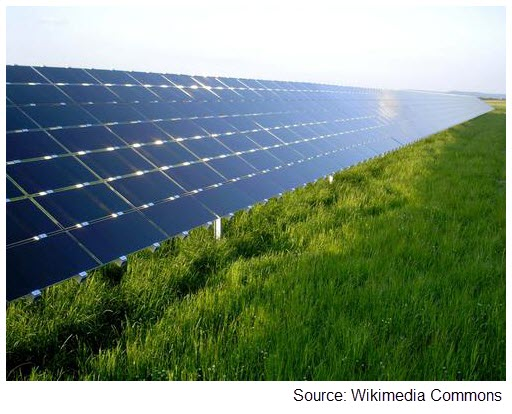 Photograph of an array of thin-film solar cells in a big, open field.