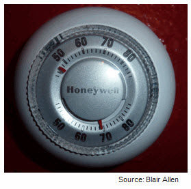 Photograph of a round electromechanical termostat with dial that shows actual temperature and set temperature.